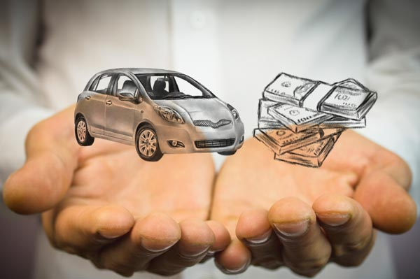 Open palms holding schematic of a car in one hand and money in the other